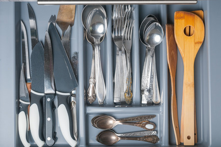 Opened kitchen drawer with cutlery. Top view
