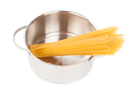 Dry spaghetti in stainless saucepan close up on white background