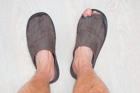 Man feet standing at wooden floor ware in ragged home slippers