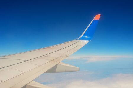 Airplane wing on blue sky and clouds background