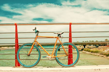 Old yellow fixed gear bicycle on a bridge Imagens