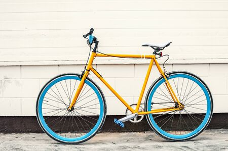 Old yellow fixed gear bicycle on white wall background