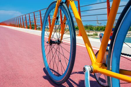 Yellow fixed gear bicycle riding on red road