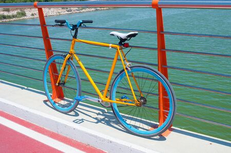 Yellow fixed gear bicycle on a bridge Imagens