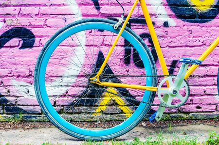 Yellow fixed gear bicycle on grunge wall background
