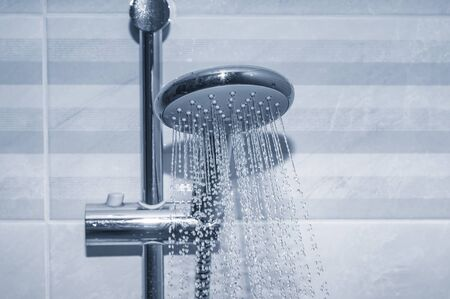 Shower faucet with running water drops close up