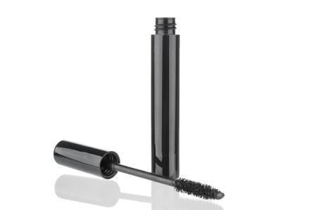 Black mascara bottle and brush close up isolated on white background