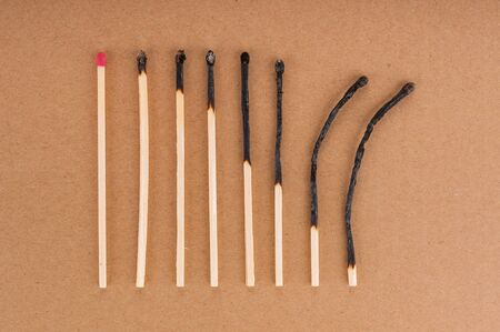Row of different burnt matches on brown background Banco de Imagens