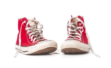Old red sneakers isolated on white background