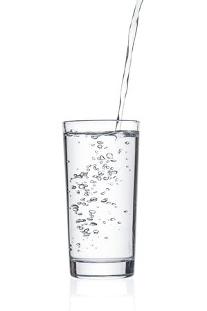 Flowing pure water into tumbler on white background
