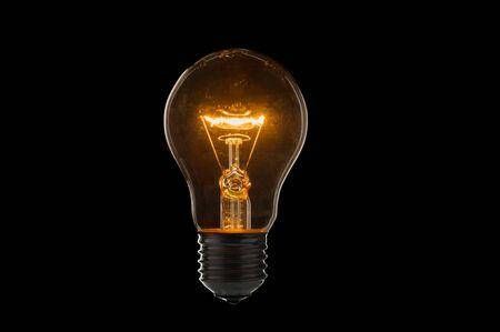 Old, dirty light bulb close up on black background Stock fotó