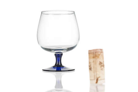 Wine glass close up and blurred wine cork on white background. Back focus