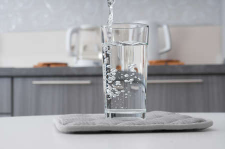 Pouring clean water into glass on a kitchen interior background
