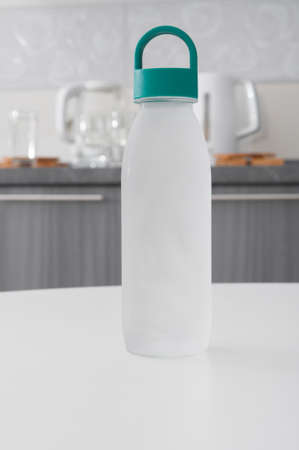 Reusable plastic bottle with cold water on a kitchen interior background