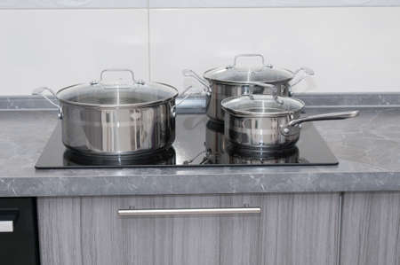 Stainless saucepans on electric stove in a kitchen