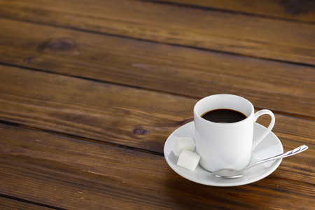 Black coffee with 2 sugars, white cup on a brown wooden table. Stok Fotoğraf