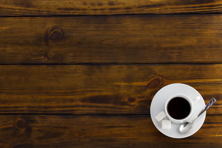 Black coffee with 2 sugars, white cup on a brown wooden table. Top view Stok Fotoğraf