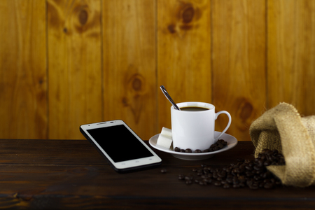 Black coffee with 2 sugars in a white cup, coffee bean on a brown wooden table. Always good for a coffee shop next to a cell phone. Stok Fotoğraf