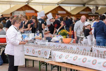 BEKESCSABA, HUNGARY - OKT 19, 2018: Sausage Festival (Csabai Kolbaszfesztival) Youth teams prepare sausages. One of the jury members