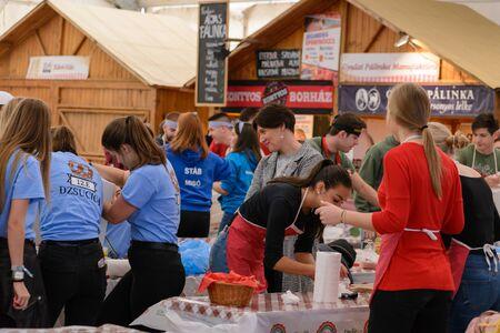 BEKESCSABA, HUNGARY - OKT 19, 2018: Sausage Festival (Csabai Kolbaszfesztival) Youth teams prepare sausages. 新聞圖片
