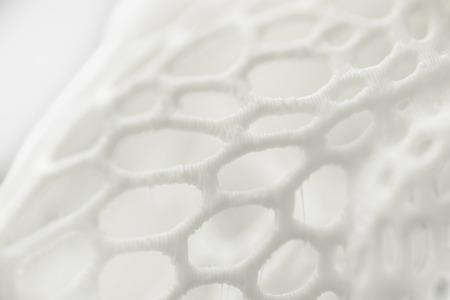 Primer plano del objeto impreso en 3D, fondo abstracto con textura de malla.