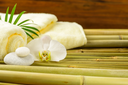 Spa towels, candle and orchid on bamboo blurred background. 版權商用圖片