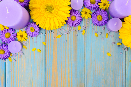 Yellow gerbera, purple garden flowers and candle on a blue wooden table. The flowers are arranged side by side. Top view, copy space.