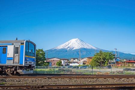 railroad tracks: Blue train on railroad tracks with Mount Fuji  at Kawaguchiko , japan in summer