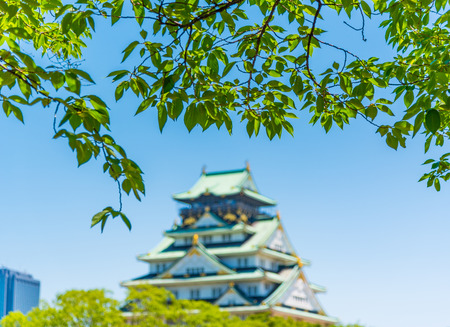 Osaka Castle with Blur effect and foreground of green leaf Editorial