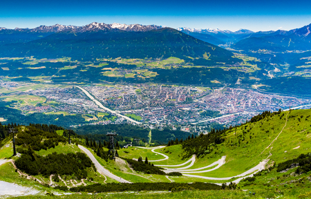 view from above of Innsbruck city with alpes mountain range, Natural path and Cable car take from Seegrube mountain