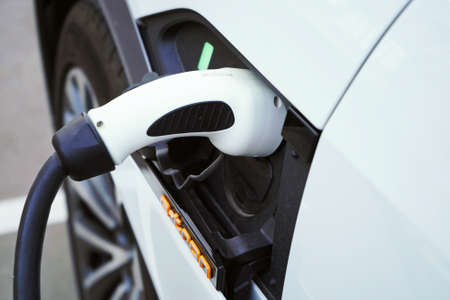 Charging a white electric car close-up.Altrernative eco energy fuel.Power supply connect to electric car for add charge to the battery.Eco-friendly alternative energy concept