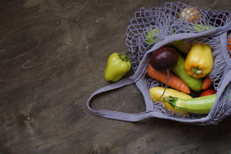 Gray bag string bag with vegetables, zucchini, bell peppers, carrots, beets, onions brown wooden background. Harvest from garden fresh bright vegetables. Concept zero waste. Copy space. Stock fotó