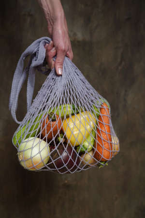 Woman holds her hand gray bag string bag with vegetables, zucchini, bell peppers, carrots, beets, onions brown wooden background.Harvest from garden fresh bright vegetables.Concept zero waste. Stock fotó