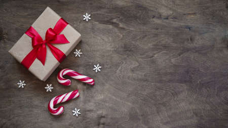 Gift box wrapped in brown paper and tied with red ribbon, Christmas candy canes and white snowflakes on wooden brown background, top view, copy space. Christmas and New Year concept.Flat, overheard. Stock fotó