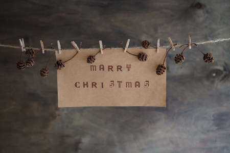 Merry christmas text written on brown paper. Christmas poster hanging on a rope with clothespins and pine cones on a brown wooden background. Christmas card concept.