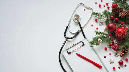 Christmas medical banner fir branches, cones, red balls, snowflakes, stethoscope and tablet on white background top view. Copyspace. Medicine new year flatly. Stock Photo