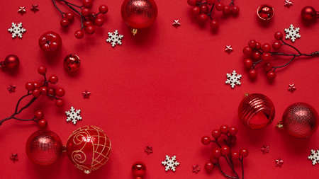 Concept for New Year and Christmas banner.Christmas decor, red balls, berries, stars and white snowflakes on a red background, top view, flat lay, copy space.Christmas card with place for text, lettering.