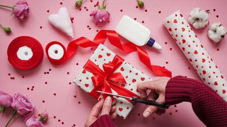 第12步,用于包裹情人节礼物的逐步说明。妇女用包裹白皮书包裹礼物在心脏并且封印边缘与胶水在桃红色背景顶视图,平的位置。