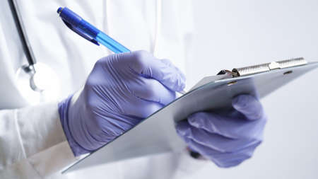 Close-up of a doctor writing a prescription in a medical record on a tablet.