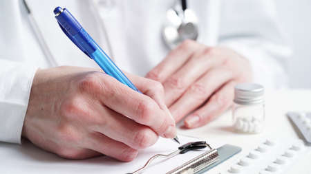 Close-up of a doctor hands writing a prescription in a medical record on a tablet. A doctor in a white coat holds pills in his hands and writes a prescription with a blue pen. Medical banner concept