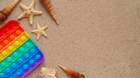 Beach summer vacation banner concept with trendy bright rainbow silicone stress relief toy.