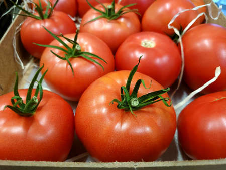 Close-up shot of a lot of ripe fresh tomatoes in a wooden box for sale at a farmer's market and in an organic store. Healthy food, vitamins. Raw vegetarian nutrition concept.