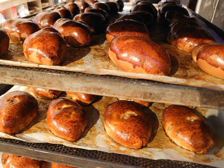 Close-up of many hot delicious pies on shelves in bakery, store. Production of bakery products. Shelf with hot pastries. Bakery, production of pies Stock Photo