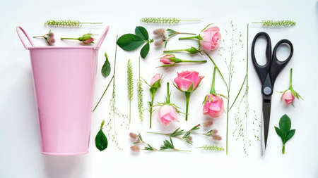 Floristic composition flat lay.Work of the florist, drawing up a flower arrangement, on a white table pink bucket, scissors, roses, flowers and herbs, top view.Floral banner.Pastel colors