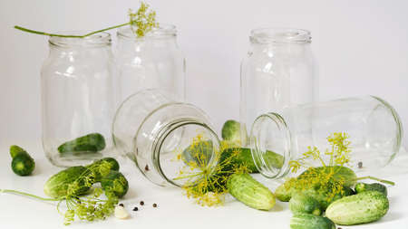 Glass jars, fresh cucumbers, dill, garlic and black pepper on a white table on a white background. Ingredients for canning, pickling or fermenting vegetables. Home recipes for pickling cucumbers