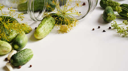 glass jars, fresh cucumbers, dill, garlic and black pepper on a white plate, top view, flat lay, copy space.Ingredients for canning, pickling or fermenting vegetables.Homemade pickling cucumber recipes
