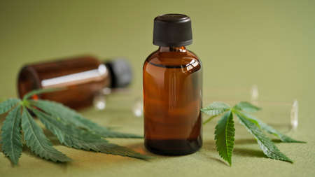 Medical Marijuana Cannabis oil extract in bottle green hemp leaves and glass test tubes on a green background.Close-up glass bottles with CBD oil, THC tincture and hemp leaves.Cosmetics CBD oil Stock Photo