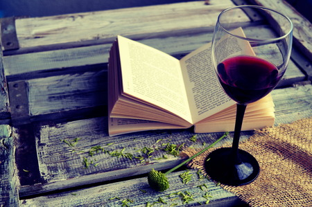 Open book with wine glass on a wooden background