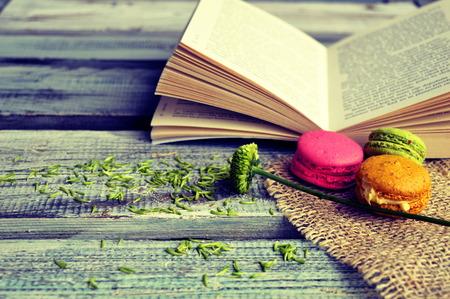 Bitterkoekjes met open boek op een houten achtergrond Stockfoto