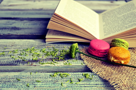 Macaroons with open book on a wooden background Imagens